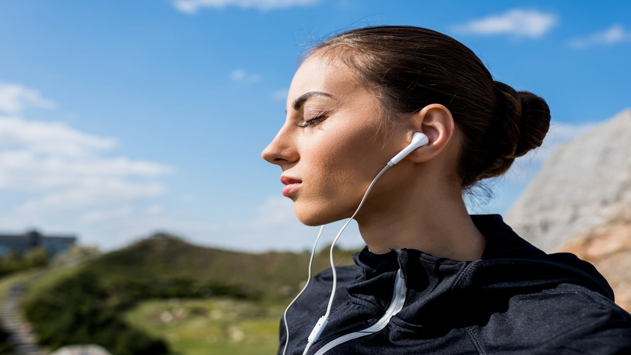 A woman with earphones and closed eyes