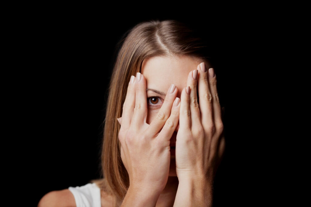 A woman covering her face with hands