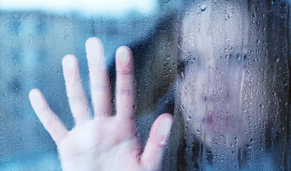 a woman behind the wet window