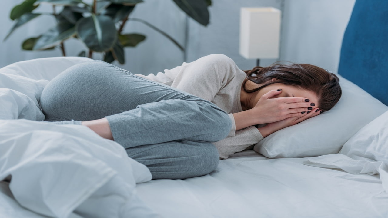 depressed woman lying in the bed