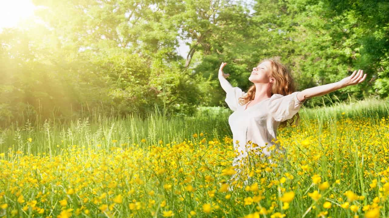 a young woman in the sun surrounded by nature