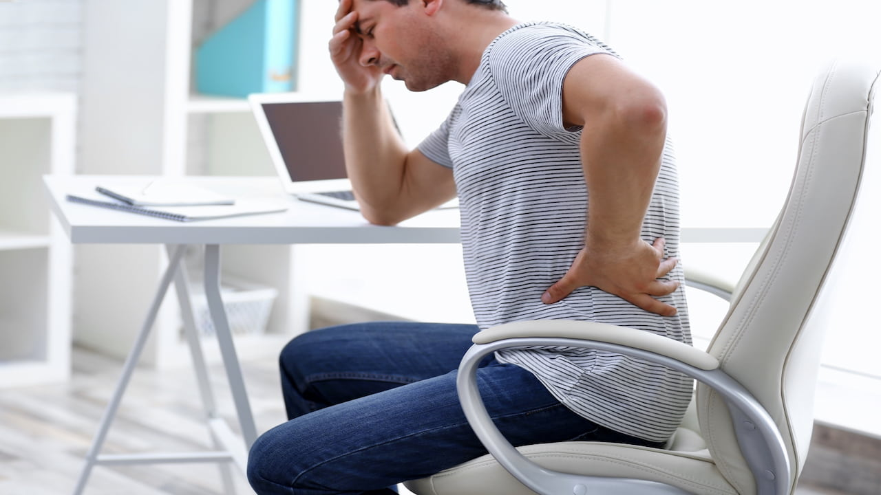 a man sitting on the chair suffering from pain