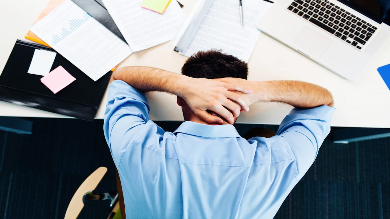 A stressed man holding his head at the work place
