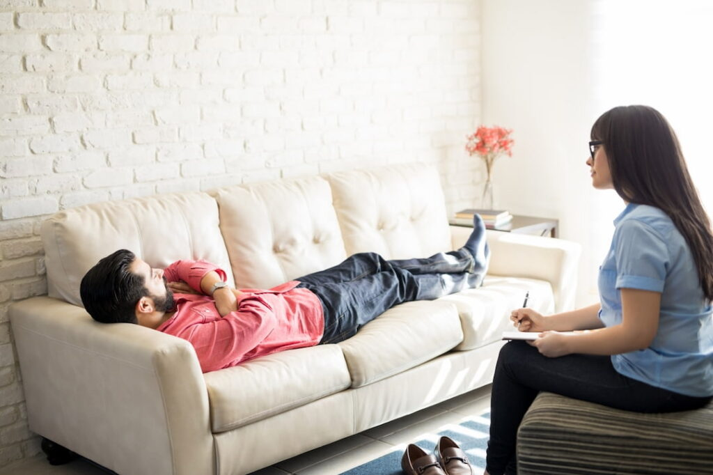 a man lying on the couch at his hypnotherapy treatment