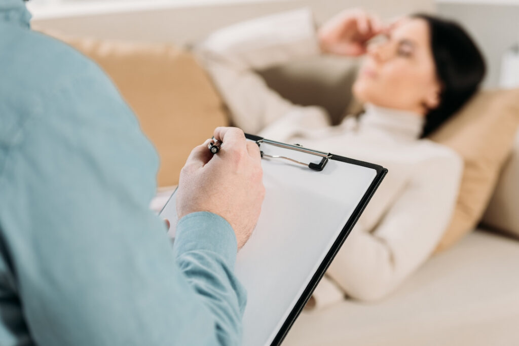a therapist holding a clipboard with notes