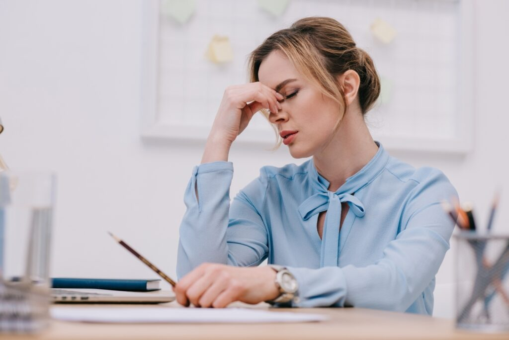Exhausted adult businesswoman sitting at workplace in office