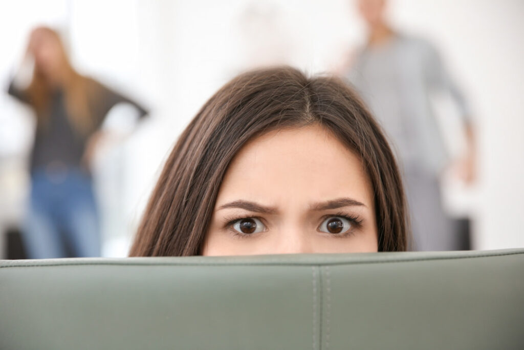 a frightened woman hiding behind the sofa