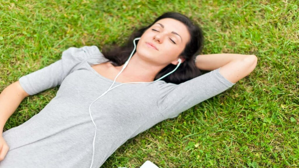 a woman lying on the grass with earphones