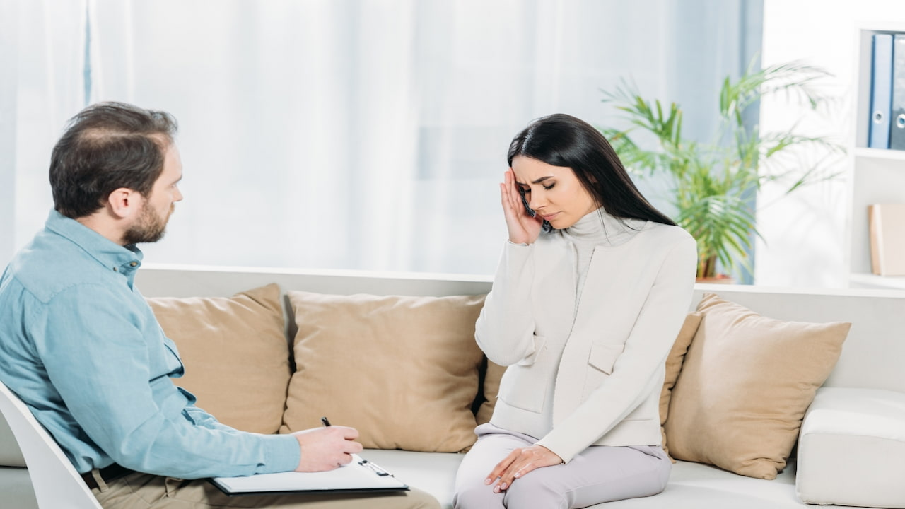 a woman sitting on the couch at her therapy session