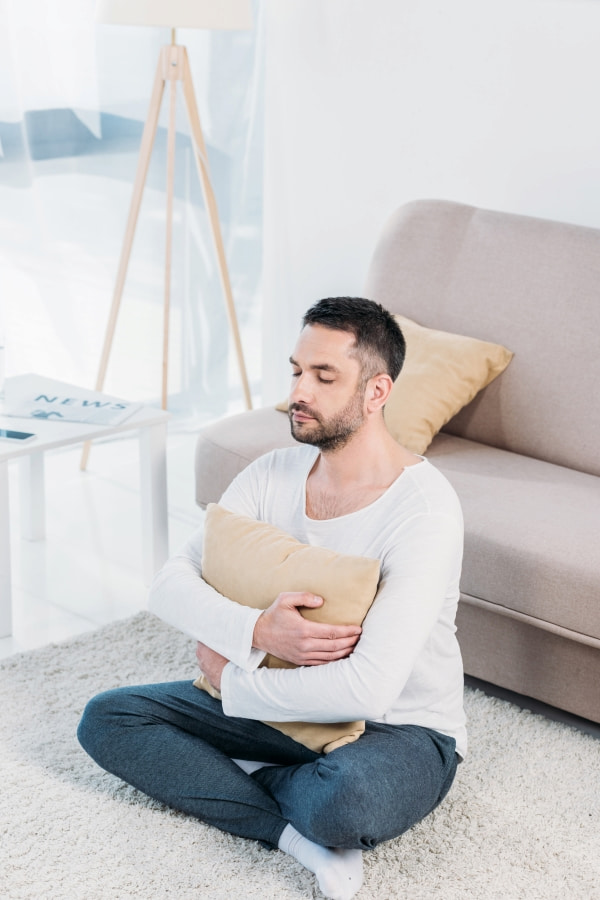 a man sitting on the carpet and holding a pillow