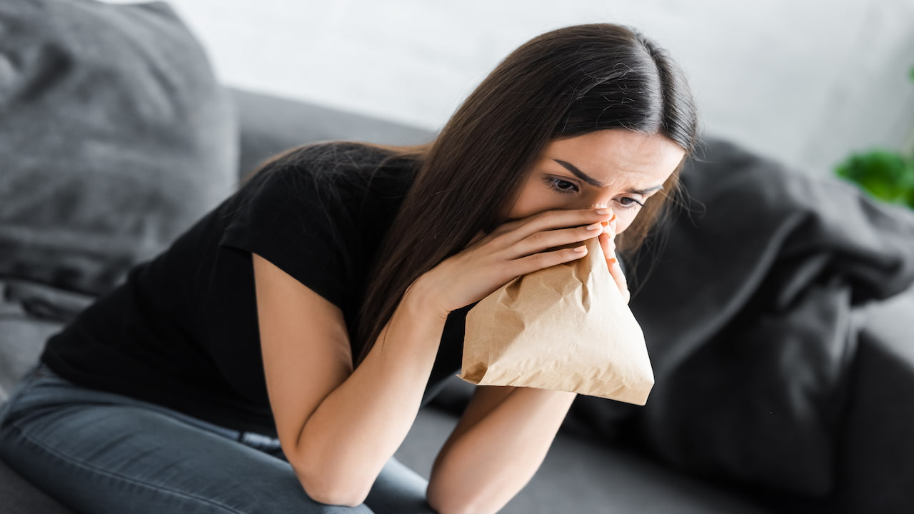 Young woman breathing into paper bag