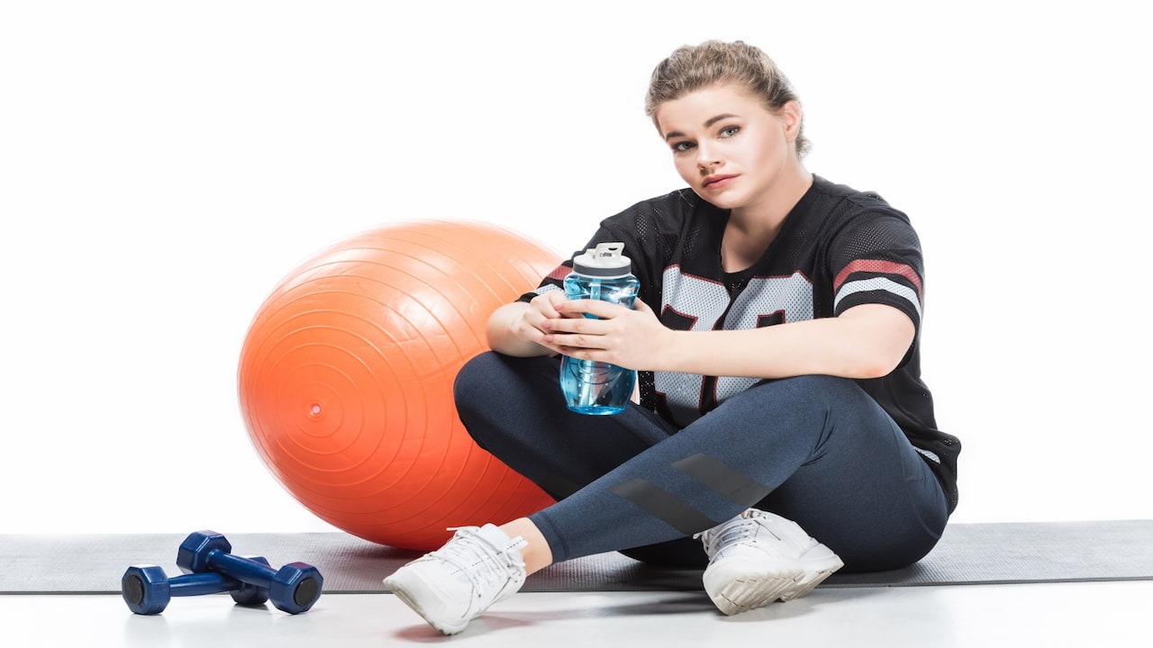 an overweight woman sitting on yoga mat