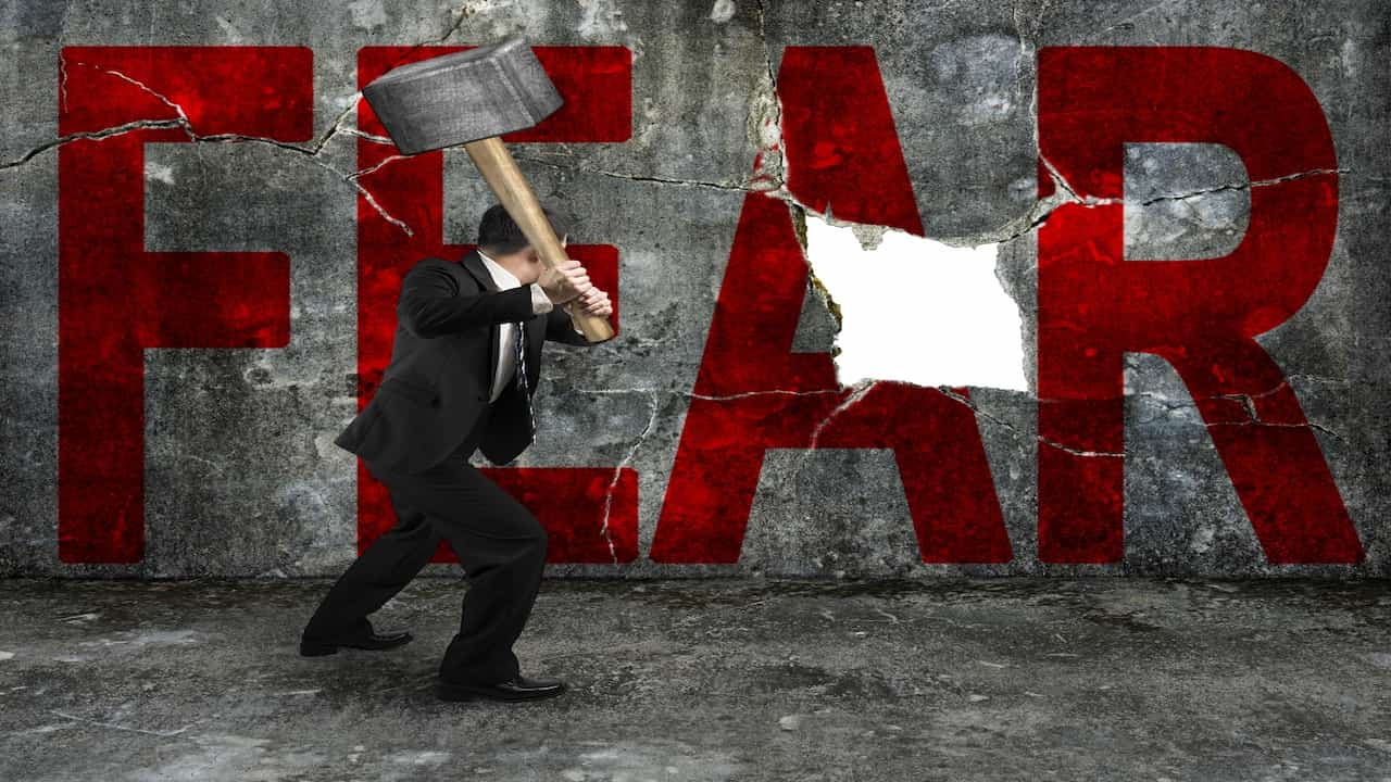 Businessman holding sledgehammer hitting red FEAR word on the wall