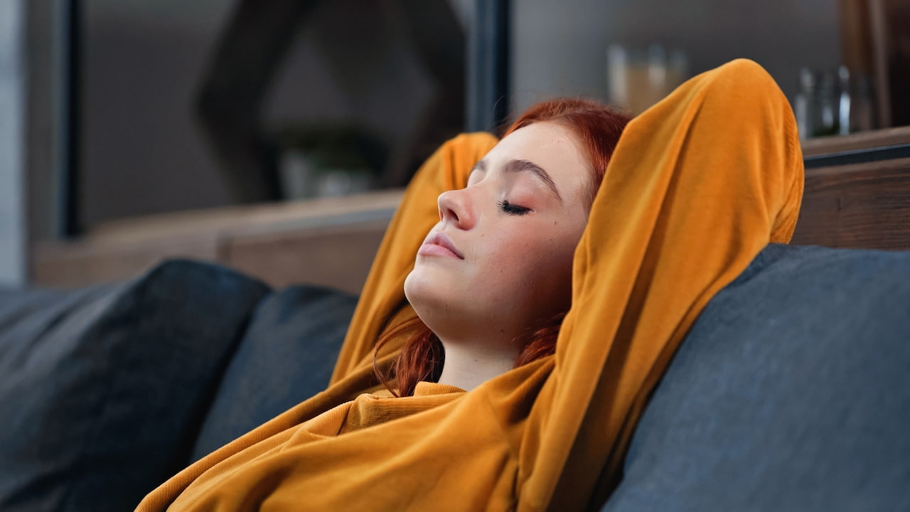 a girl in yellow sweater sitting on the couch with her eyes closed