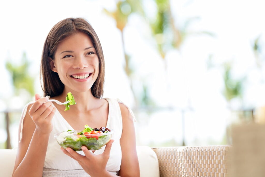 a young smiling woman eating healthy food