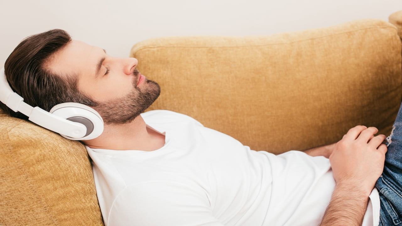 A man lying on the couch with headphones on his head
