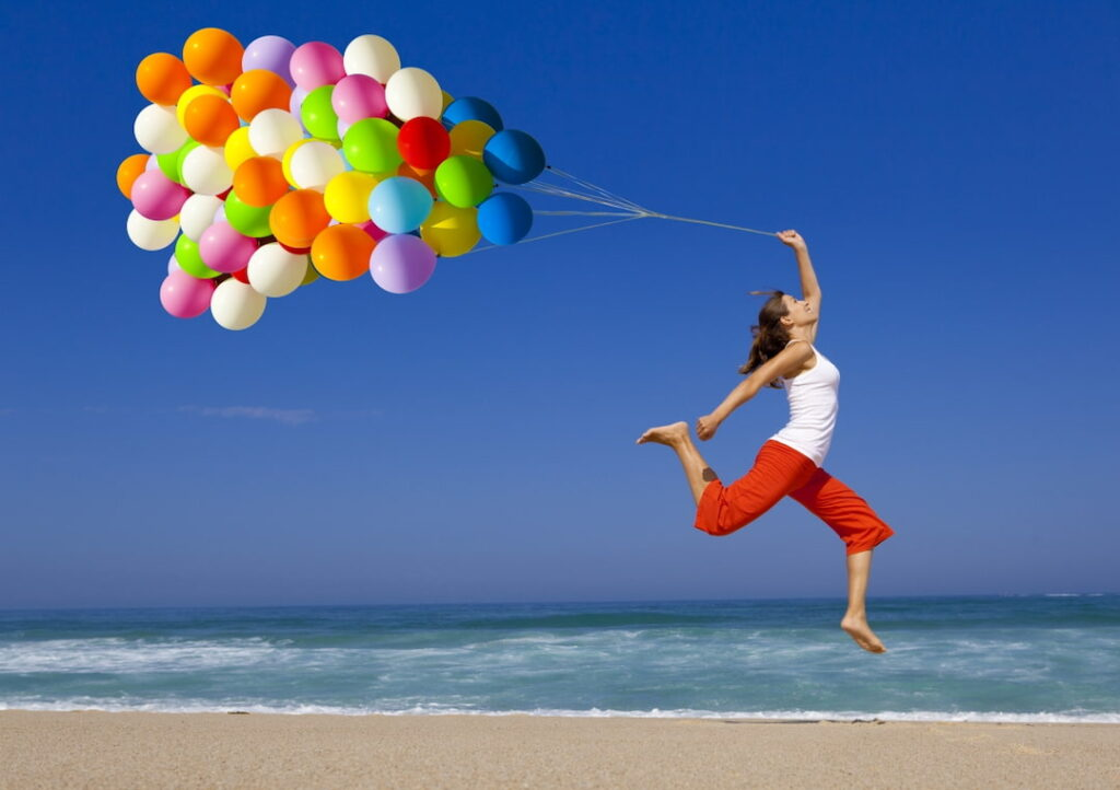 a young woman holding balloons and jumping by the sea