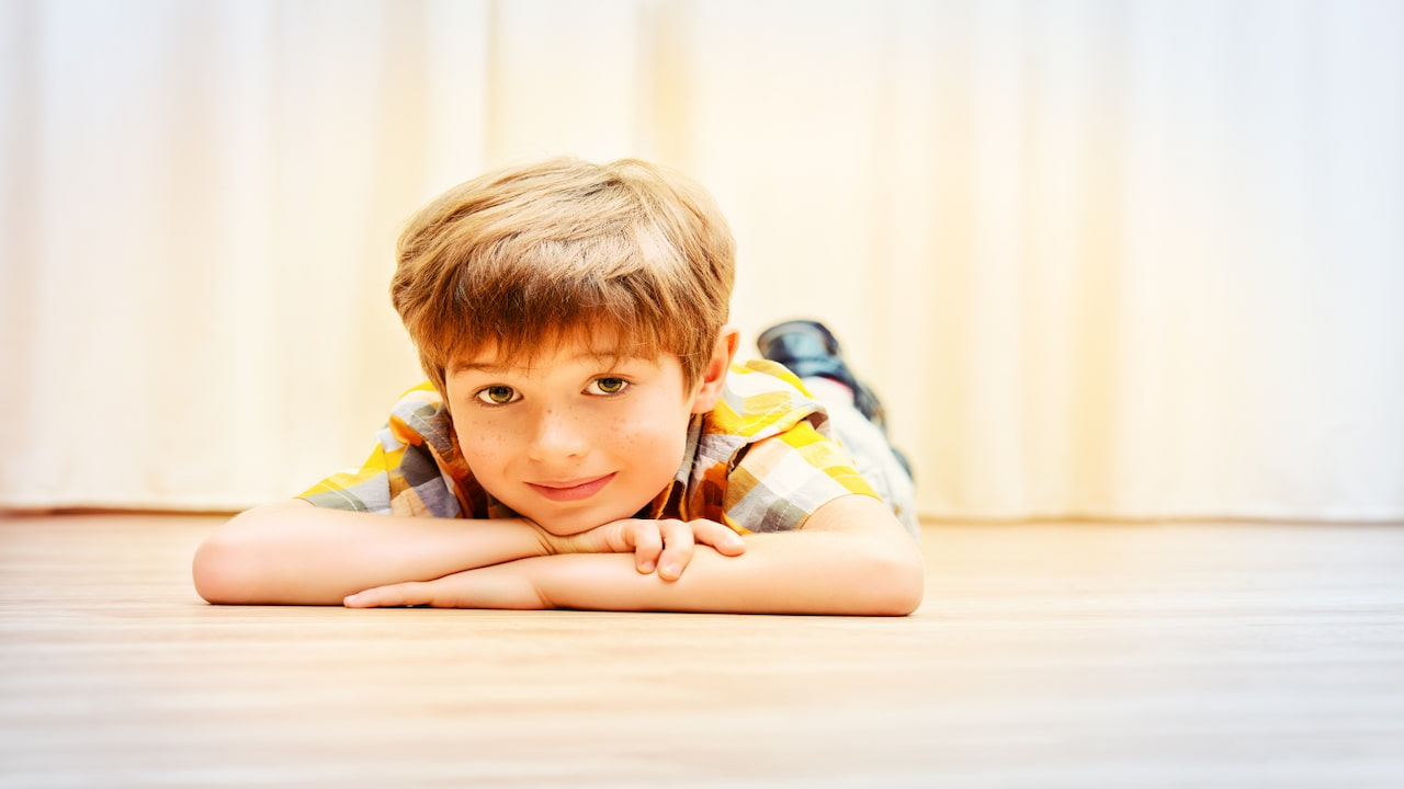 a boy lying down with hands under his chin