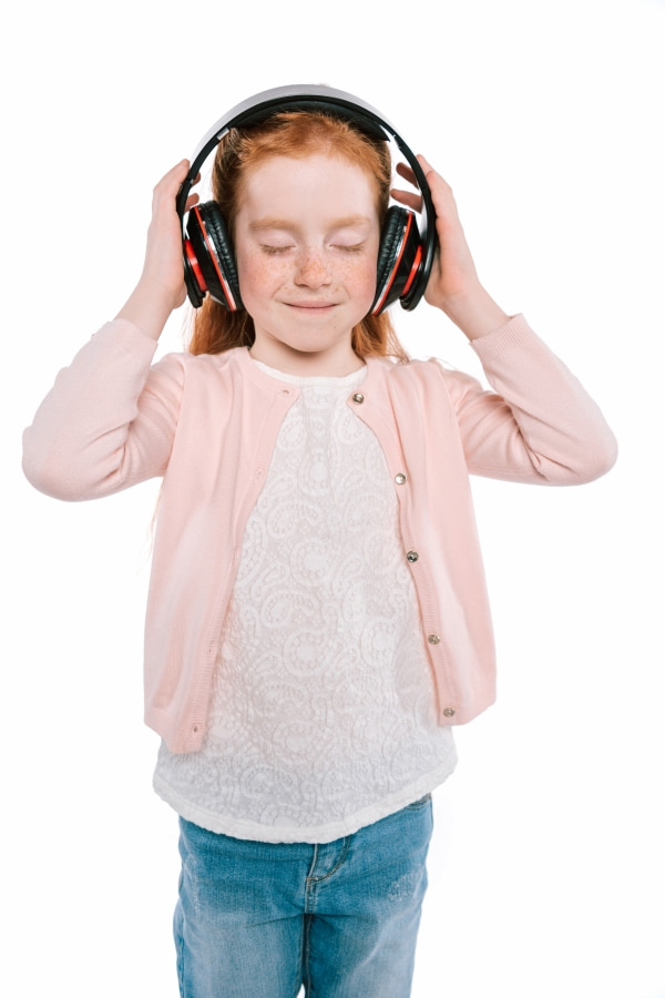 a girl with her eyes closed holding headphones on her head