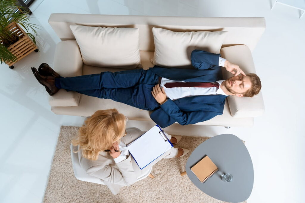 a man lying down on the couch during the hypnotherapy session
