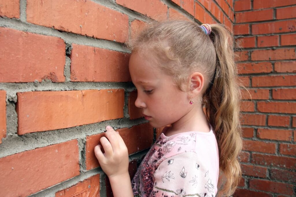sad girl leaning against the brick wall