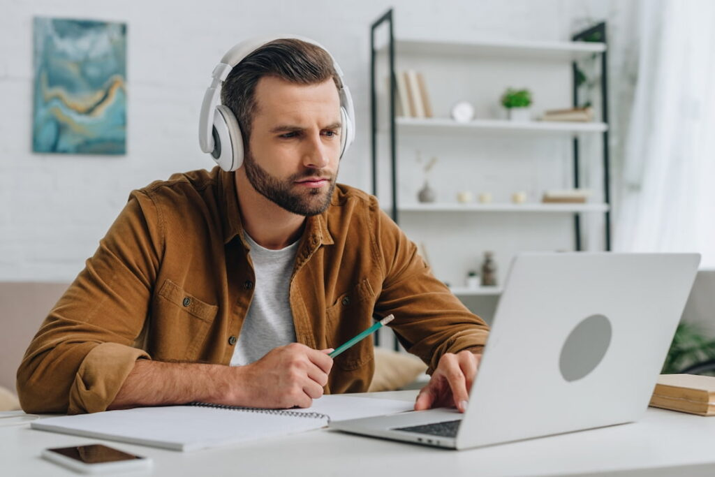 a man with headphones looking at his laptop and making notes