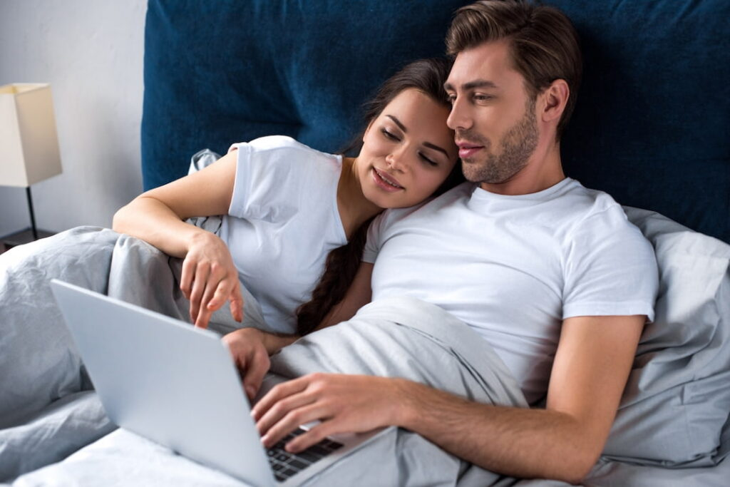 a man and a woman lying in the bad and watching video on the laptop