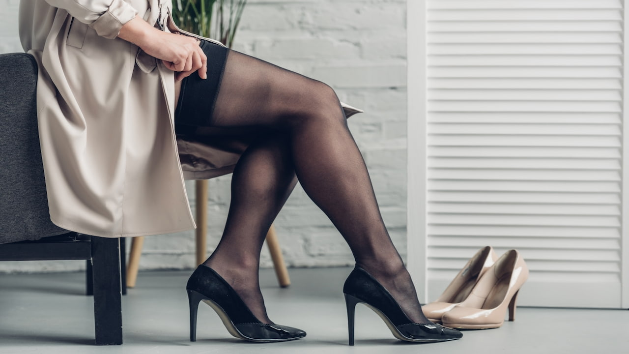 Cropped shot of trans man in trench coat putting on stockings