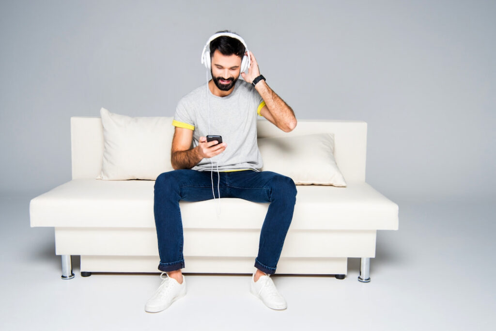 young bearded man with white headphones on his head sitting on the couch