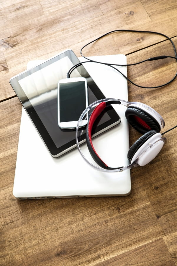 laptop, tablet, cellphone and headphones on the table