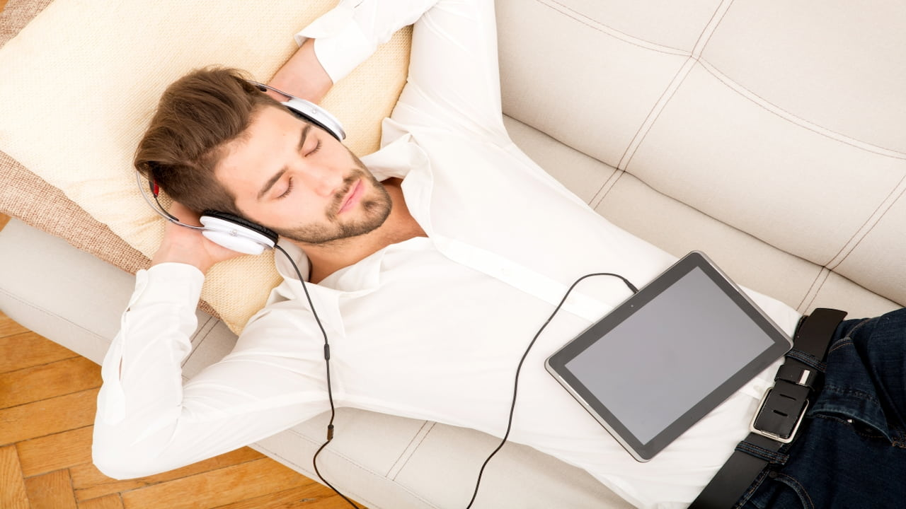 a man lying on the sofa with tablet and headphones