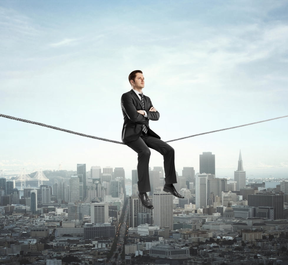 a man in a suit sitting on the rope above the city