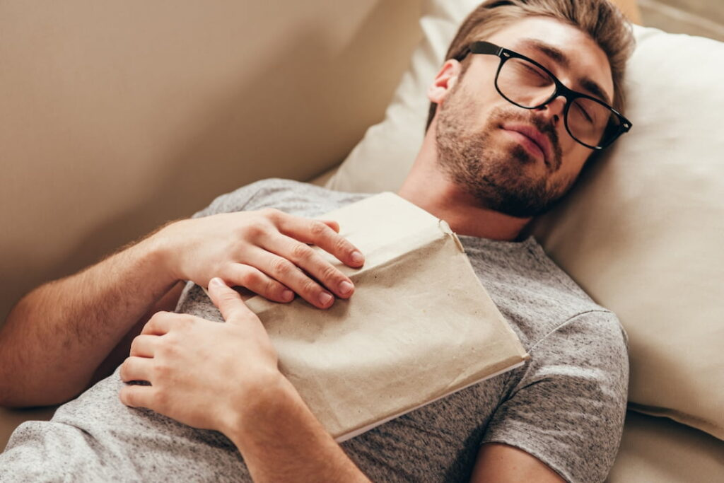 a man sleeping with a book on his chests