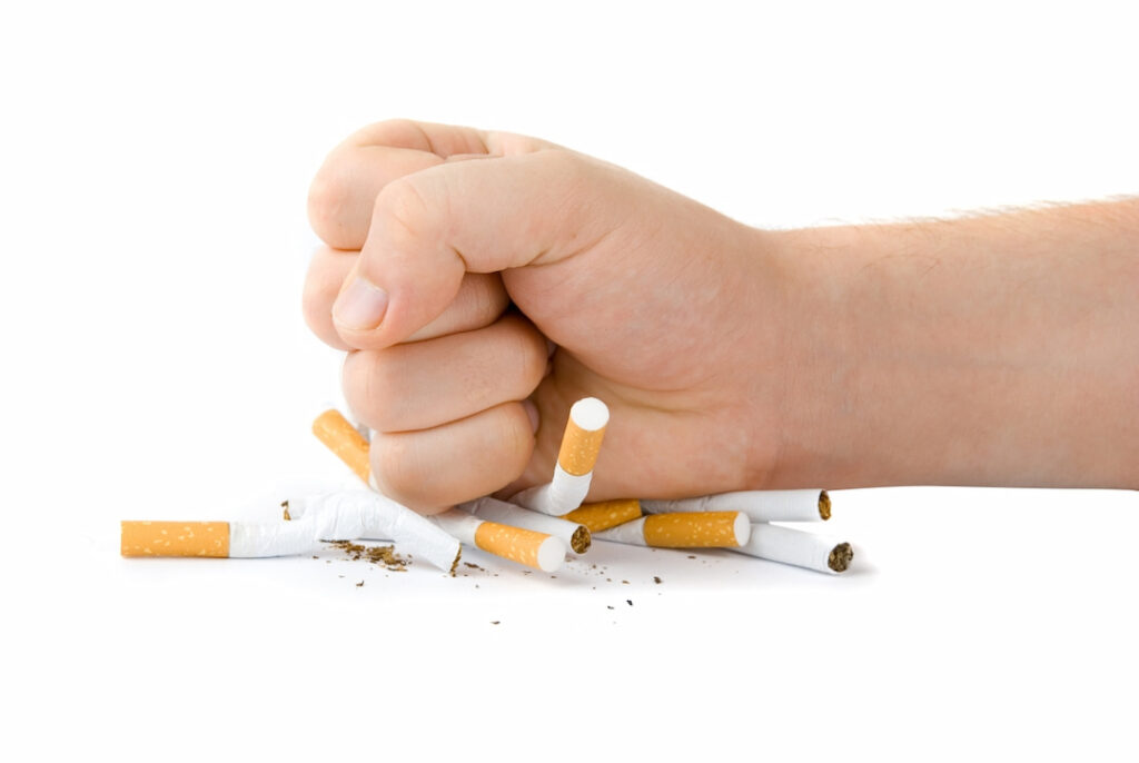 a fist smashing the cigarettes