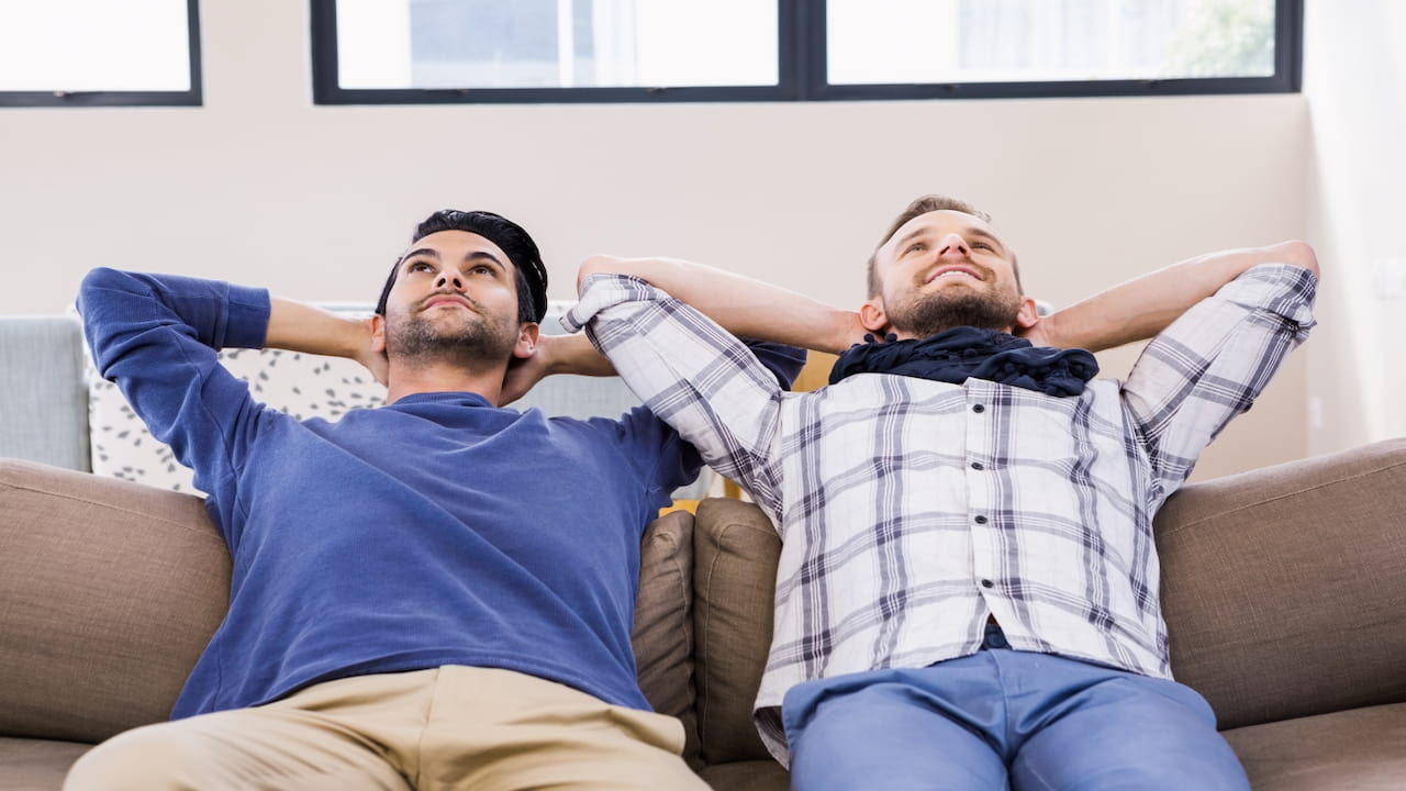 two men next to each other relaxing on the couch