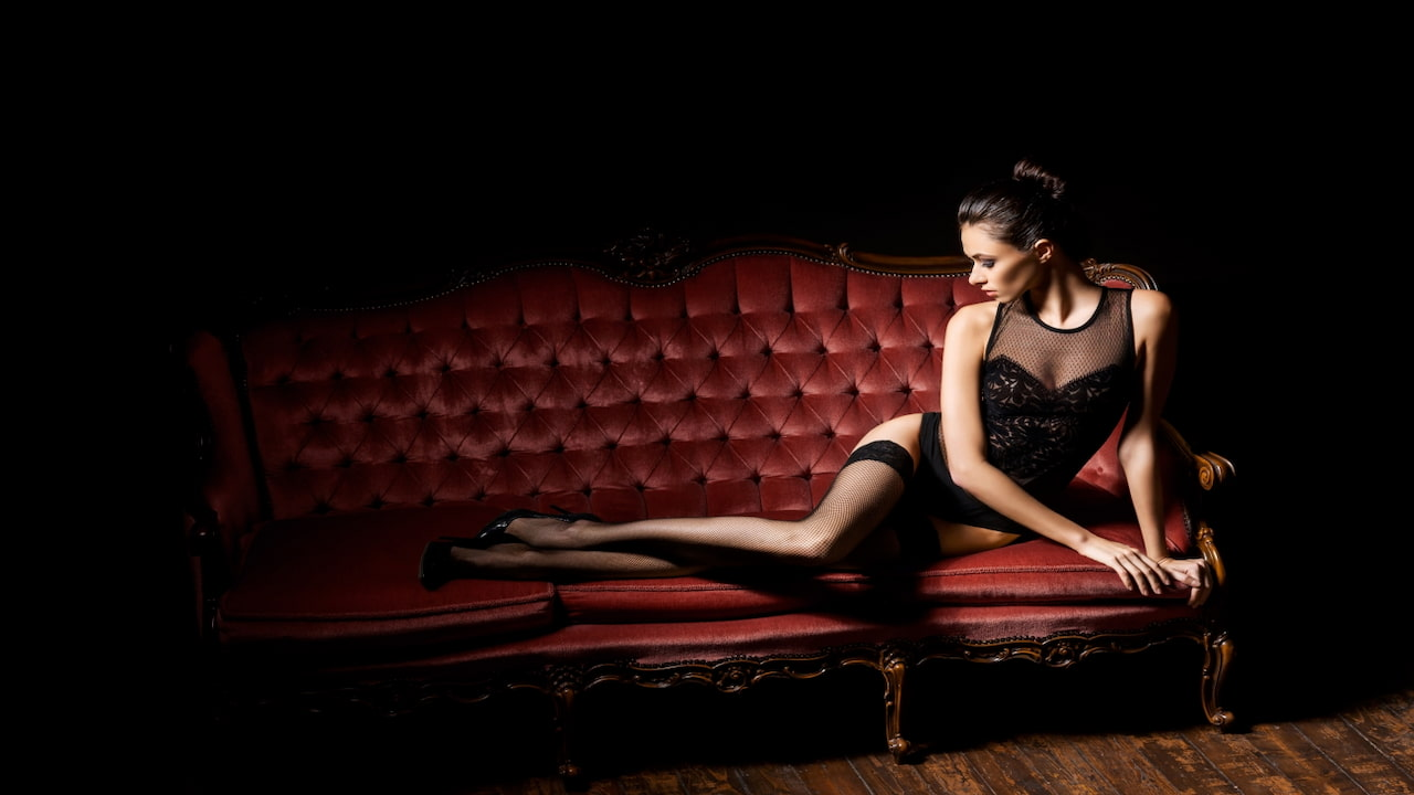 woman in lingerie posing on the dark red sofa