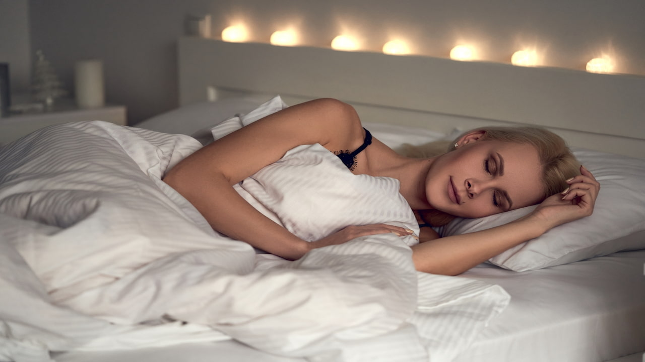 Attractive young woman sleeping comfortably in cozy bed