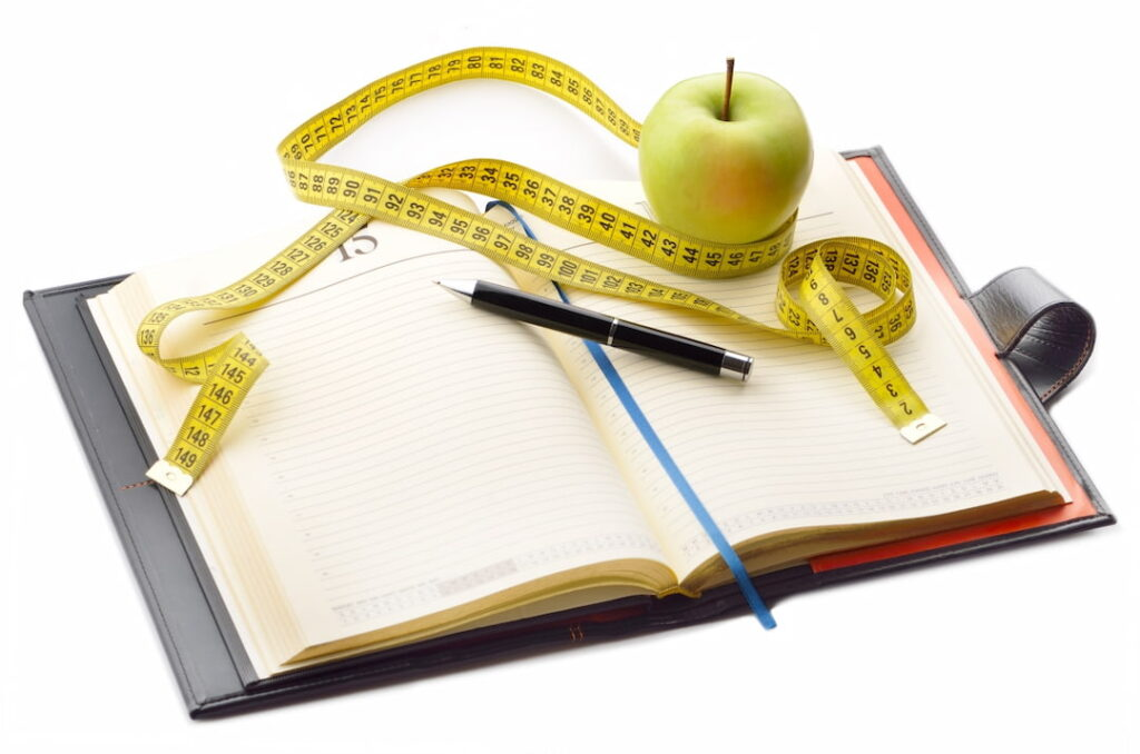 an apple, a pencil and a food diary