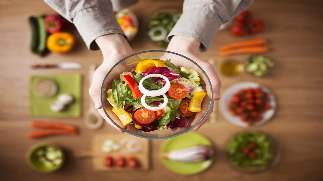 a person holding the bowl with healthy fresh homemade salad
