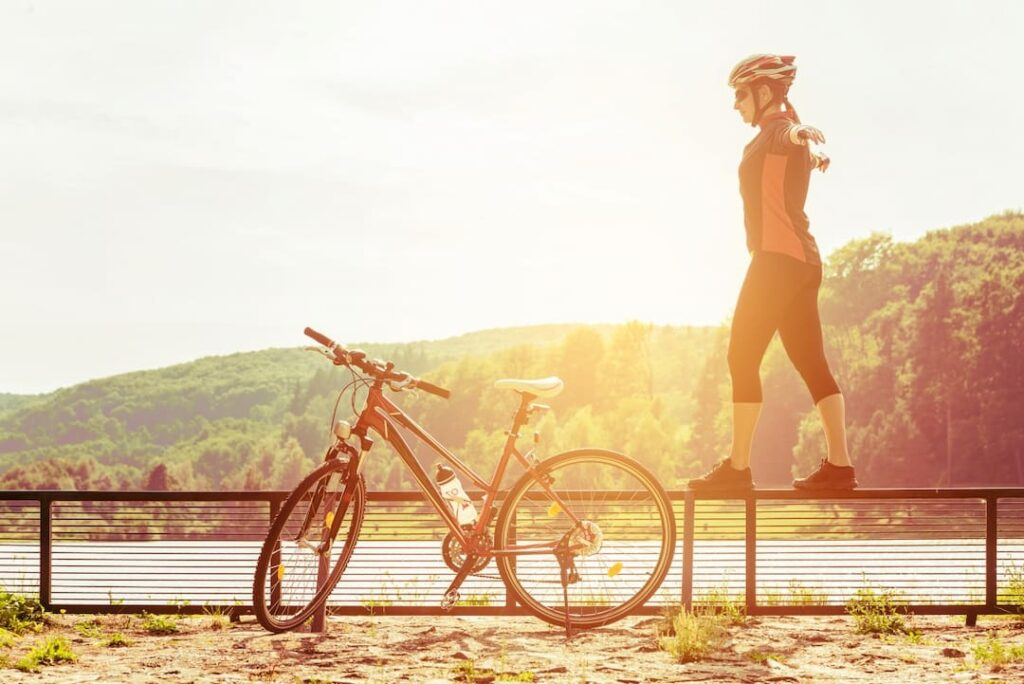 woman standing on the fence by her bicycle