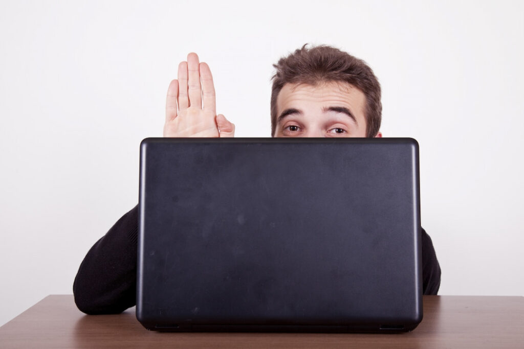 a man hiding behind the opened laptop