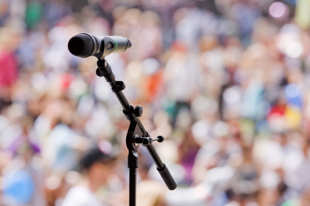 an open microphone with a crowd audience in the background