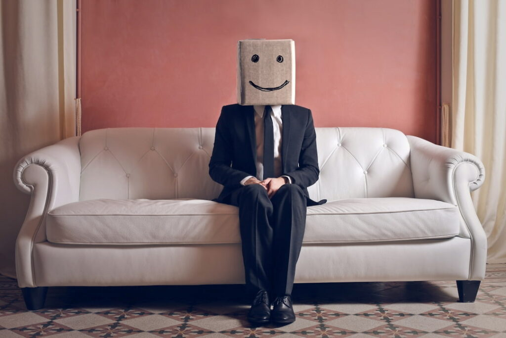 a man sitting on the couch with a box over his head