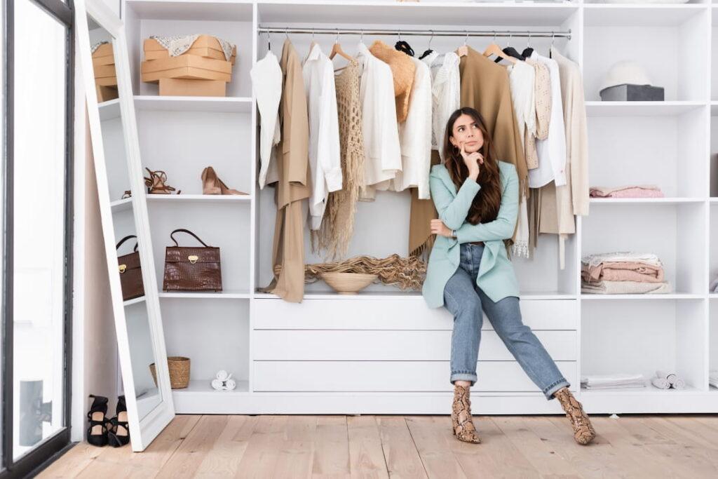 Pensive woman sitting on the shelf in the wardrobe