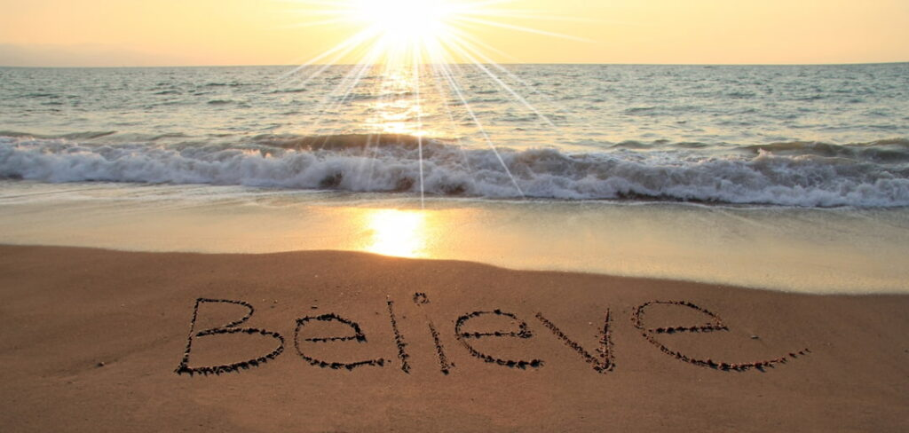 word Believe written on the sand