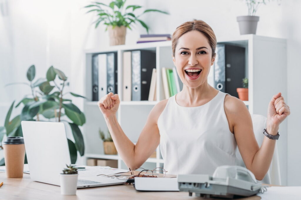 a woman celebrating success at workplace