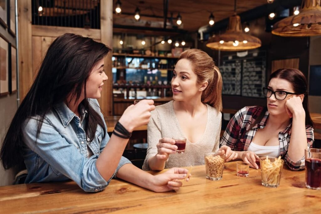 3 girls in a bar talking