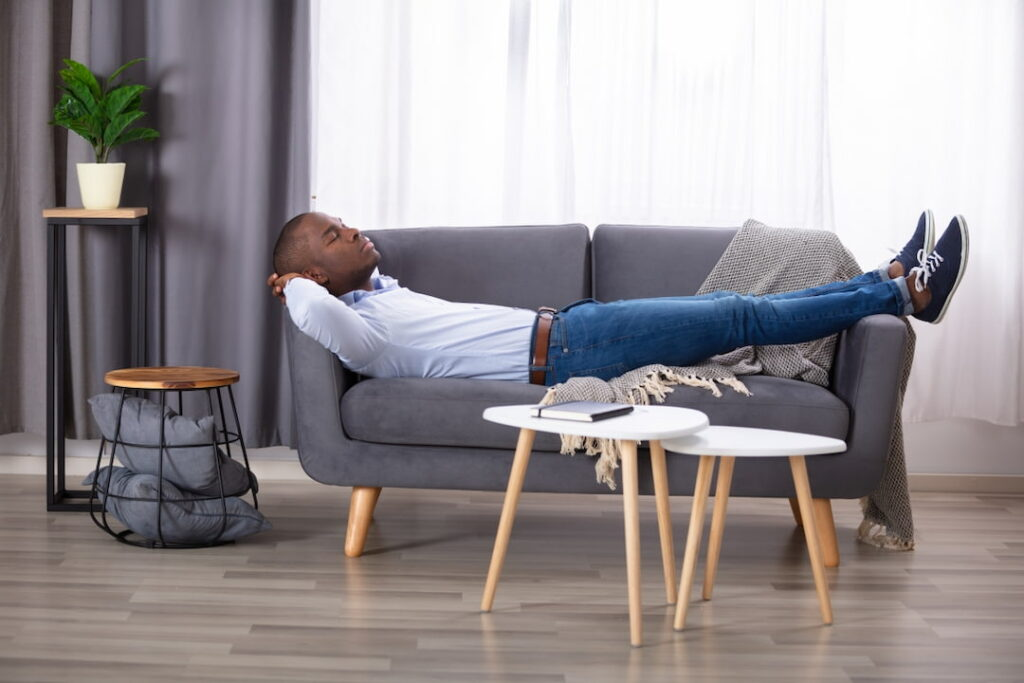 a man lying on the sofa in his living room