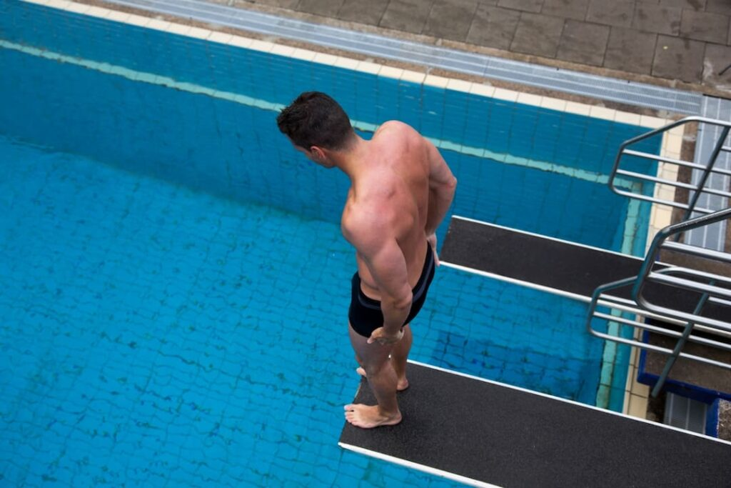 man standing on diving board and looking down to the pool water