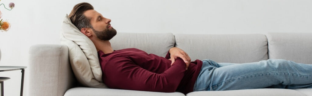 man relaxing on the couch with his eyes closed